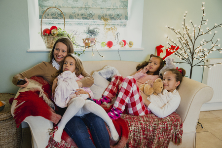 Three little girls are relaxing on the sofa with their mother at christmas time, watching the television. Stock Photo