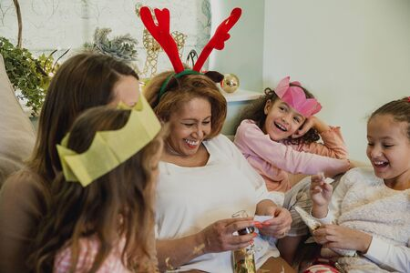 Cheerful grandmother is reading a joke from a christmas cracker to her granddaughters and their mum. Фото со стока