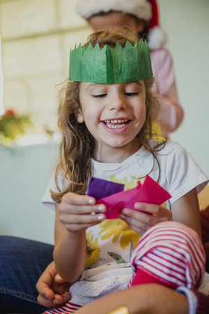 Happy little girl is playing with all the hats from the christmas crackers in her home at christmas time.