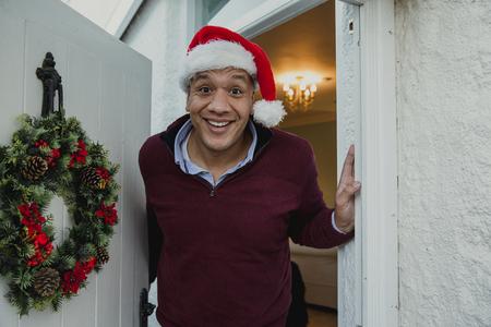 Oogpunt dat van een vrolijke mens in een santahoed wordt geschoten die u welkom heten in aan zijn huis voor Kerstmis.
