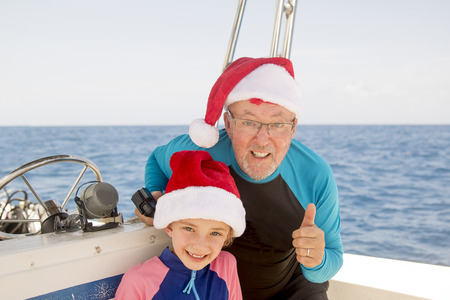 Father and daughter pose for the camera while enjoying a boat holiday at christmas.