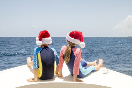 Siblings sit on the front of a boat in the Caribbean and enjoy the sun at Christmas time. Stock Photo