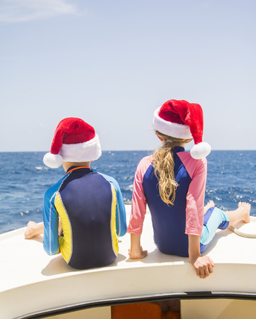 Siblings sit on the front of a boat and enjoy the sun at Christmas time.