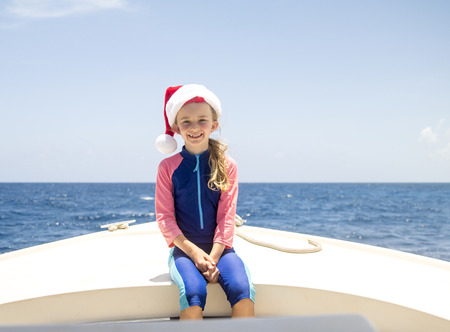 Little girl is posing for the camera on a boat in the Caribbean at christmas time. She is wearing a santa hat.