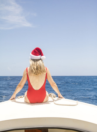 Senior woman sits on the front of a boat and enjoys the Caribbean sun at Christmas.