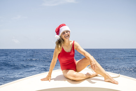 A woman sits on the front of a boat and enjoys the winter sun at Christmas. Stock Photo