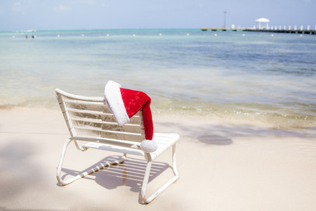 A santa hat rests on a chair on a summer beach in the caribbean.