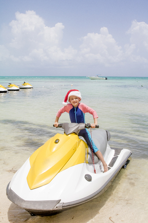 Little girl sits on a jetski in the Cayman islands whilst smiling at the camera at Christmas time. Stock Photo