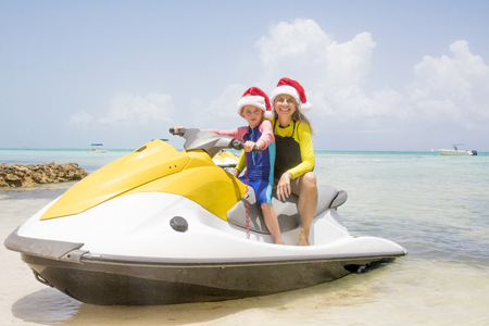 Mother and daughter pose together on a jetski in the Cayman Islands at Christmas time.