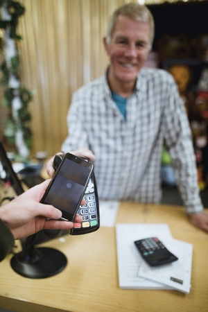 Making a smart payment in a shop using a mobile phone.