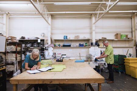 シニアの実業家は彼女の在庫の倉庫で書類をやっています。彼女の夫は、背景布をアイロンでは。