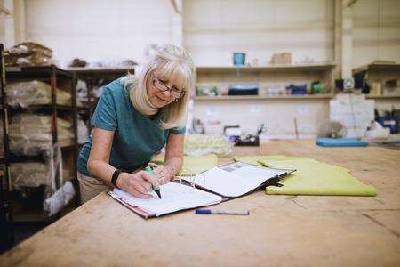 シニア実業家は彼女の在庫の工場で事務をやっています。