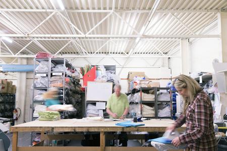 Drukke werknemers in een textielfabriek. Ze drukken en sorteren stof en materiaal.