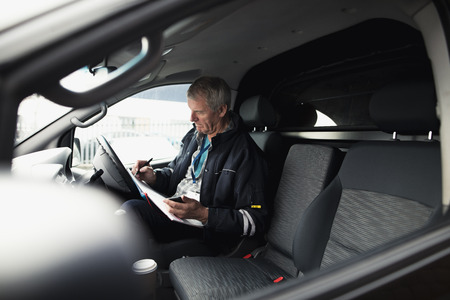 Businessman is working in the driver seat of his car while stationary. He is filling in paperwork and holding a smart phone.
