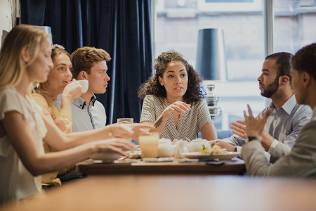동료의 그룹은 레스토랑에서 아침 식사를 즐기면서 회의가 있습니다. 스톡 콘텐츠