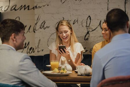 Friends are enjoying a meal in a restaurant. One woman is laughing while looking at her smartphone.