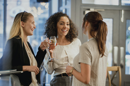 Three businesswomen are enjoying glasses of wine at a bar after work.  Banco de Imagens