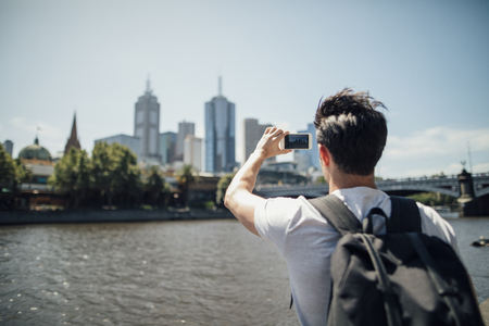 Millennial tourist is using his smart phone to take photos of the cityscape from Yarra River bank in Melbourne, Victoria.