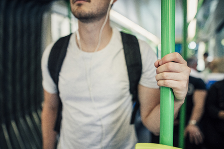 Close up shot of a millennial man holding a pole while travelling on a tram in Melbourne, Victoria.