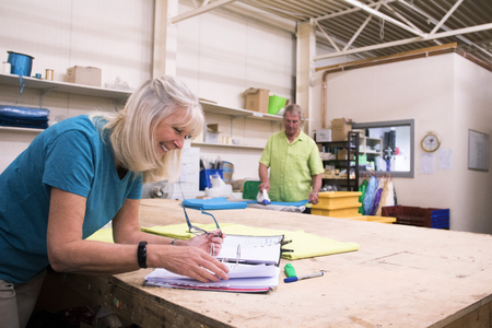 Senior businesswoman is doing paperwork in her stock warehouse. Her husband is in the background ironing fabric.  写真素材