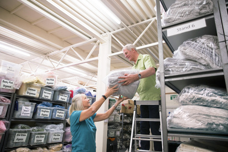 Senior businesspeople are working together to stock a textile warehouse.  Stock Photo