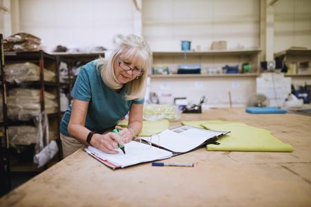 Senior businesswoman is doing paperwork in her stock factory.  写真素材