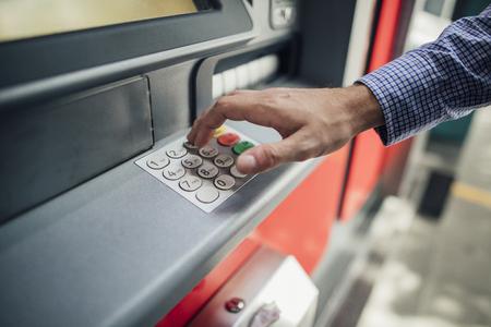 Schließen Sie herauf Schuss der Hand eines Geschäftsmannes, die Tasten auf einer Geldautomaten drückt, um Geld herauszuholen. Standard-Bild - 89876351