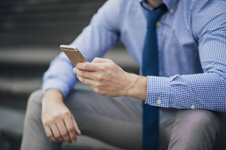 Businessman is sitting on the steps of an office building while using his smart phone.