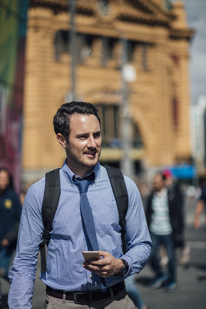 Millennial businessman is commuting to work in Melbourne, Victoria. He is walking while holding a smartphone.