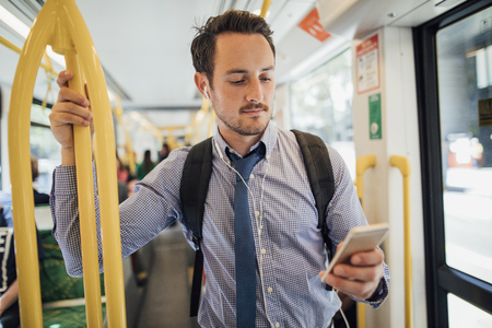 Millennial businessman is commuting on a tram in Melbourne, Victoria. He is watching something on his smart phone with headphones while standing and holding on to the rail. Stok Fotoğraf - 100485560