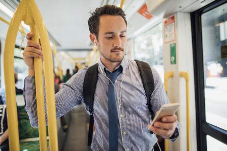 Un hombre de negocios milenario viaja en un tranvía en Melbourne, Victoria. Él está mirando algo en su teléfono inteligente con auriculares mientras está de pie y agarrado a la barandilla.