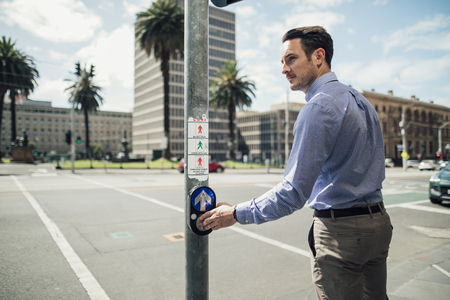 Millennial businessman is using a public crossing while commuting in Melbourne, Victoria.