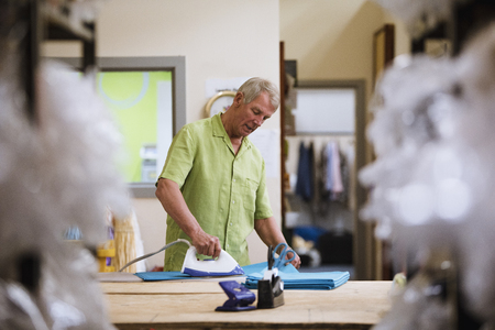 Senior man is ironing fabrics in the business factory.