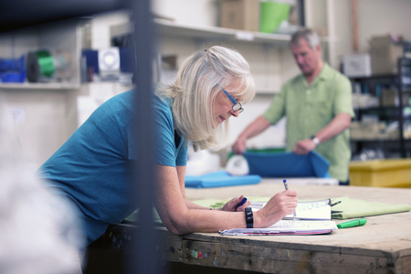 Senior businesswoman is doing paperwork in her stock warehouse. Her husband is in the background measuring fabric.  Stockfoto