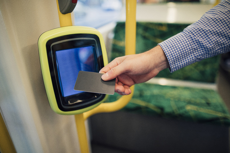 Close up shot of a commuting businessman scanning his travel card on a tram in Melbourne, Victoria. Archivio Fotografico