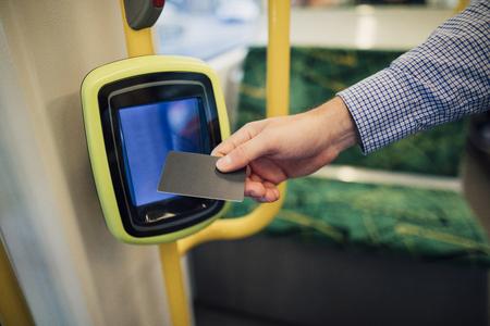 Ciérrese encima de tiro de un hombre de negocios de conmutación que explora su tarjeta de viaje en una tranvía en Melbourne, Victoria. Foto de archivo