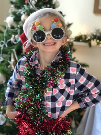 Little girl is posing for the camera in front of the christmas tree. She is wearing festive sunglasses and has tinsel wrapped round her.  Reklamní fotografie