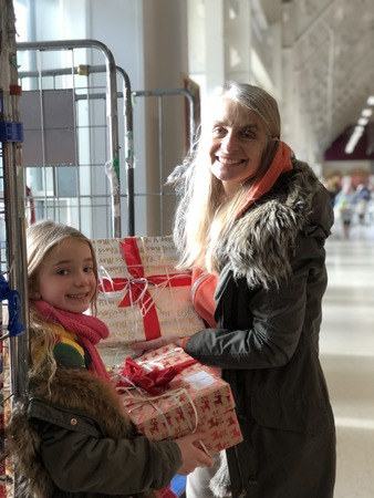 Little girl and her mother are giving donation boxes to a charity for christmas.