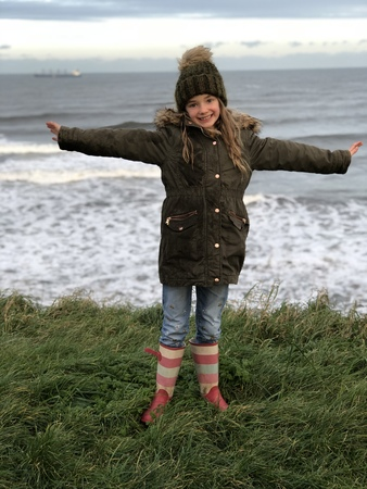 Little girl is posing in front of the sea at the beach. she has her arms outstretched and is looking at the camera.