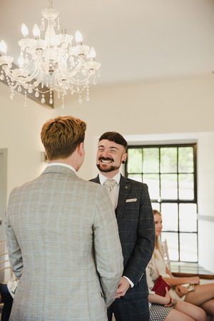 Two men are exchanging vows on their wedding day. Stock Photo