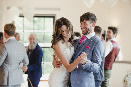 Newly wed couple are dancing together on their wedding day with all of their guests.  Stock Photo