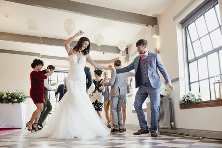 Newly wed couple are enjoying dancing with all of their guests on their wedding day.