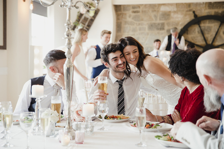 Bride is socialising with her guests at the meal on her wedding day.