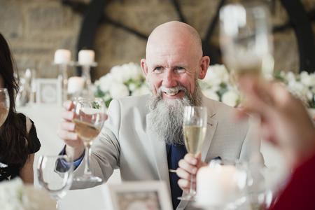 De hogere mens heft zijn glas op een toost op zijn maaltijd van het dochtershuwelijk op.