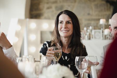 Moeder van de bruid heft haar glas op tot een speech toast tijdens de maaltijd op de bruiloft van haar dochter.
