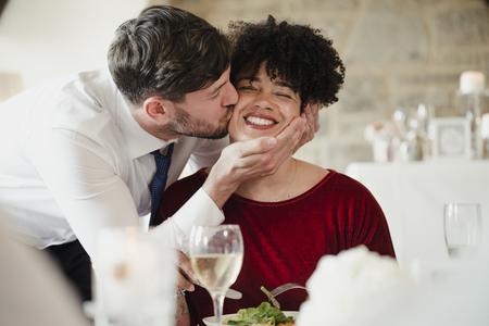 Huwelijksgasten die pret hebben bij de maaltijd. Een vrouw met een afro krijgt een dikke kus op de wang van de bruidegom op zijn trouwdag.
