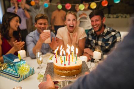 Verjaardagscake die aan een menigte mensen op een verjaardagspartij wordt gebracht.