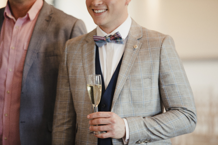 Close up shot of a man in a suit holding a glass of champagne while talking to people at a social event.