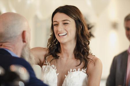 Mooie bruid deelt een dans met haar trotse vader. Ze lachen met hun armen om elkaar heen.