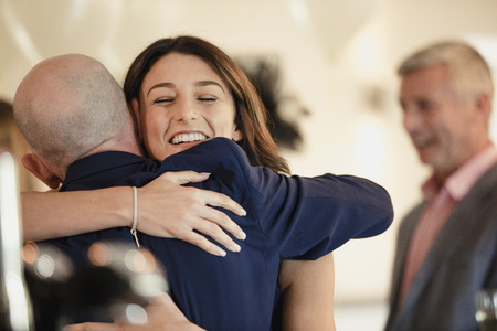 Beautiful bride is sharing a dance with her proud father. They are laughing while hugging with their arms around each other. Archivio Fotografico